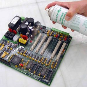 A hand spraying VpCI-238 on a circuit board